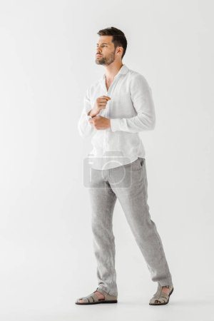 young man in linen clothes posing isolated on grey background