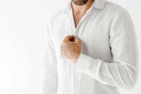 cropped image of male model unbuttoning linen white shirt isolated on grey background