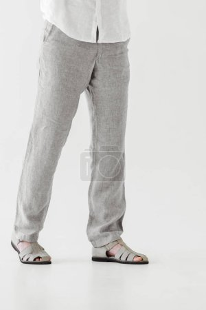 cropped image of male model in linen trousers and sandals isolated on grey background