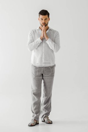 handsome man in linen clothes holding hand palms together isolated on grey background