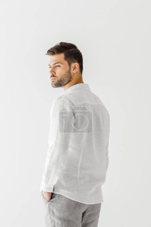 rear view of man in linen white shirt posing isolated on grey background