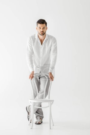 young man in linen clothes standing near chair isolated on grey background