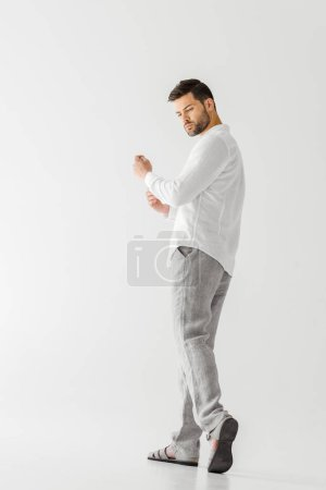 low angle view of man in linen white shirt looking away isolated on grey background