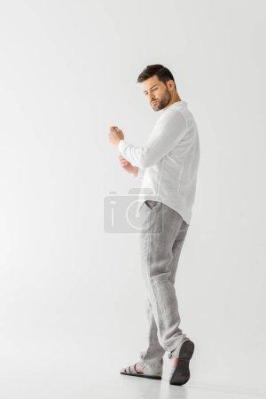 Photo pour Vue à angle bas de l'homme en lin chemise blanche regardant loin isolé sur fond gris - image libre de droit