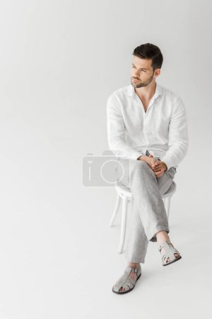 man in linen clothes sitting on chair isolated on grey background
