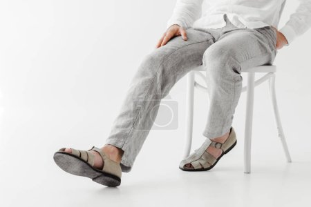 cropped image of male model in linen clothes sitting on chair isolated on grey background