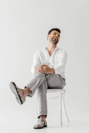 Foto de Laughing man in linen clothes sitting on chair isolated on grey background - Imagen libre de derechos