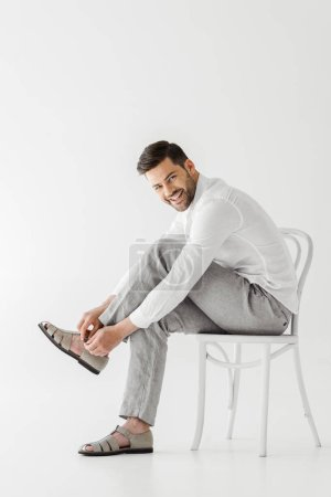 smiling man in linen clothes sitting on chair and putting on sandals isolated on grey background