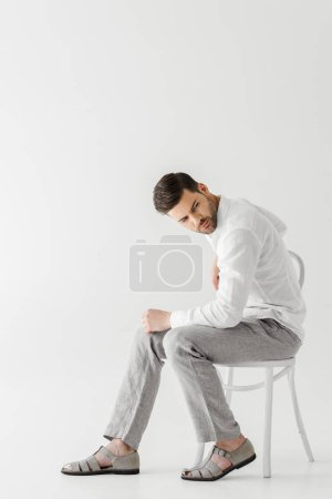 man in linen clothes sitting on chair looking away isolated on grey background