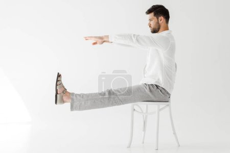 side view of male model in linen clothes sitting on chair with outstretched legs and hands isolated on grey background