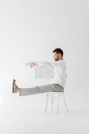 profile of male model in linen clothes sitting on chair with outstretched legs and hands isolated on grey background