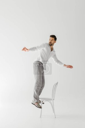 Photo for Man in linen clothes with wide arms standing on chair isolated on grey background - Royalty Free Image