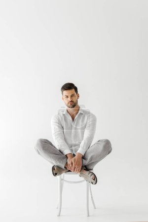 serious man in linen clothes sitting on chair isolated on grey background