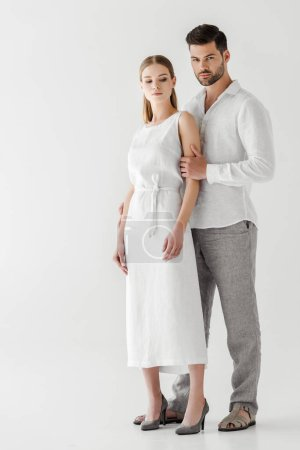 young couple in linen clothes posing isolated on grey background