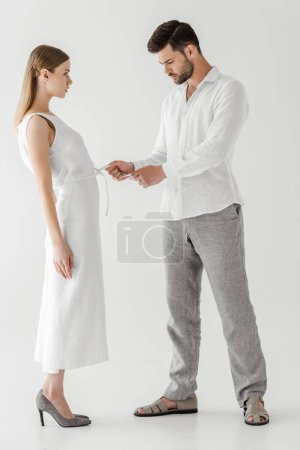 side view of male model untying white linen dress of girlfriend isolated on grey background