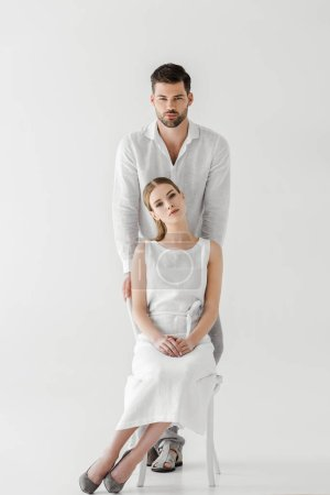 attractive woman in linen white dress sitting on chair while her boyfriend standing behind isolated on grey background
