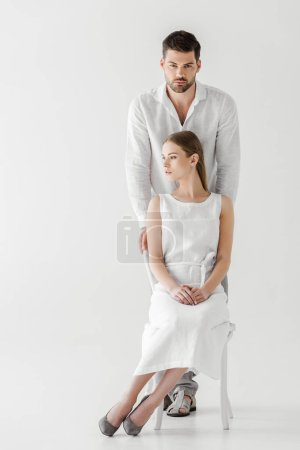 woman in linen white dress looking away sitting on chair while her boyfriend standing behind isolated on grey background