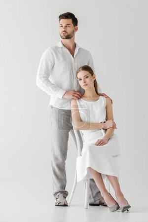 handsome man embracing girlfriend in linen white dress sitting on chair isolated on grey background
