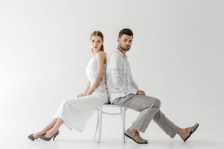 couple in linen clothes sitting back to back on chair isolated on grey background