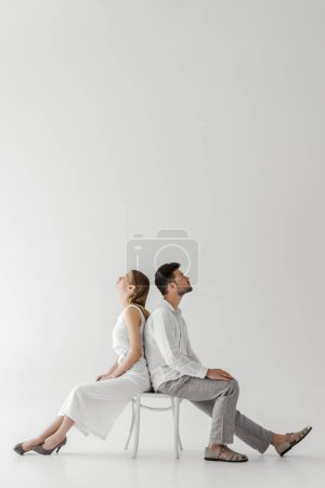 side view of young couple of models in linen clothes sitting back to back on chair isolated on grey background