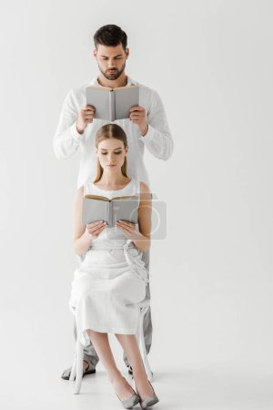 focused couple in linen clothes reading books isolated on grey background