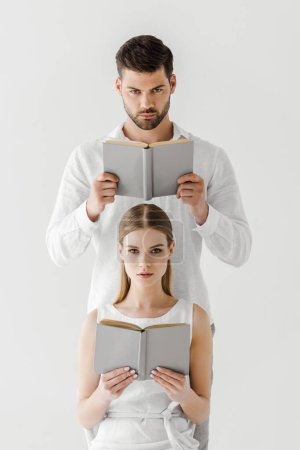 serious couple reading books isolated on grey background