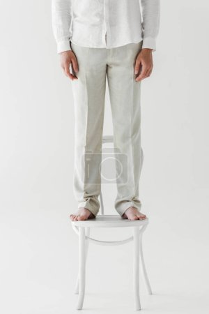 cropped image of man in linen clothes standing on chair isolated on grey background