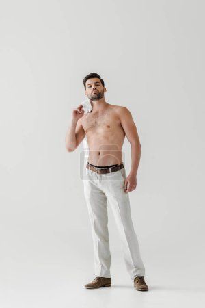 shirtless handsome man posing with shirt on shoulder isolated on grey background