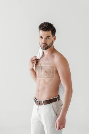 serious shirtless handsome male model posing with shirt on shoulder isolated on grey background