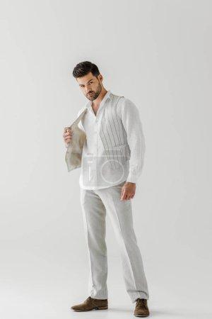 Foto de Hombre guapo en ropa ropa posando aislada sobre fondo gris - Imagen libre de derechos
