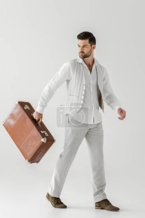 stylish male tourist in linen clothes carrying vintage suitcase isolated on grey background