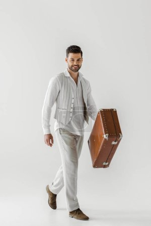 Foto de Smiling stylish male traveler in linen clothes carrying vintage suitcase isolated on grey background - Imagen libre de derechos