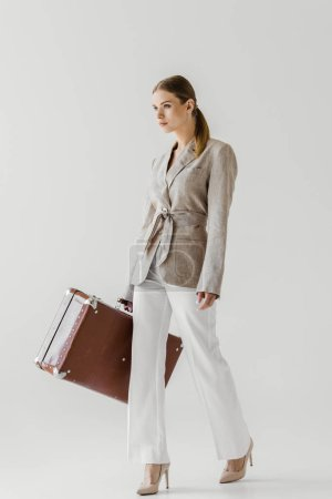 confident stylish female tourist in linen jacket holding vintage suitcase isolated on grey background