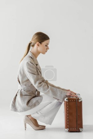 side view of stylish young female traveler in linen jacket opening vintage suitcase isolated on grey background