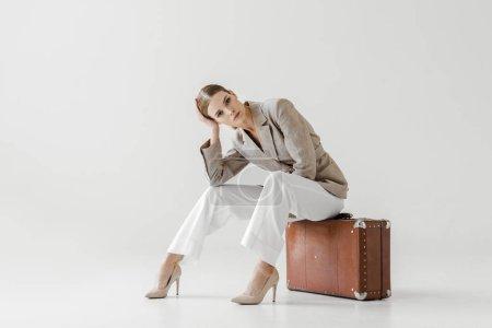 Photo pour Jeune modèle féminin chic en veste lin assis sur la valise vintage et regardant la caméra isolée sur fond gris - image libre de droit