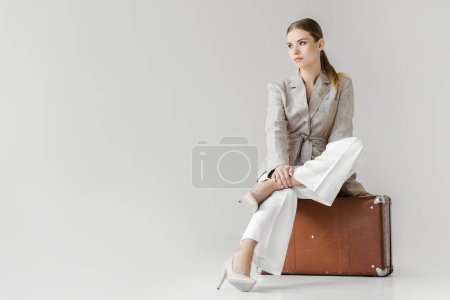 Photo pour Femme élégante en veste de lin assise sur une valise vintage et regardant loin isolé sur fond gris - image libre de droit