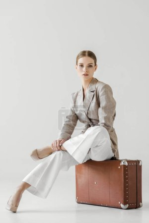 young stylish female tourist sitting on vintage suitcase isolated on grey background