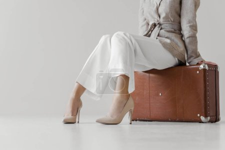 cropped image of stylish woman in linen jacket sitting on vintage suitcase isolated on grey background