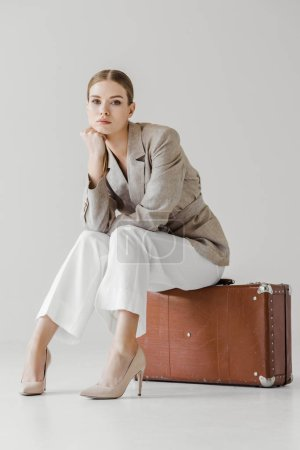 stylish young female model in linen jacket with hand on chin sitting on vintage suitcase isolated on grey background