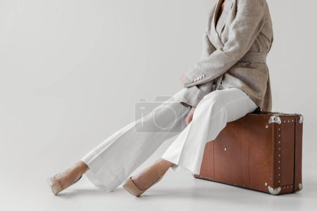 cropped image of stylish woman in linen jacket sitting on vintage suitcase isolated on grey background