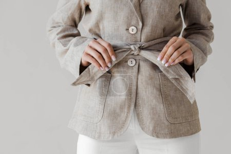cropped image of woman holding belt of linen jacket isolated on grey background