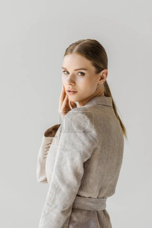 sensual young woman in vintage jacket looking at camera isolated on white