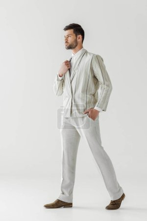 serious young man in vintage stylish suit on white