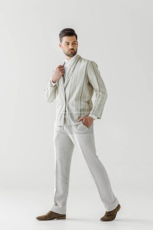 attractive young man in vintage stylish suit on white