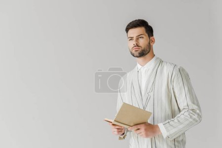 thoughtful young man in vintage striped jacket holding book and looking away isolated on white