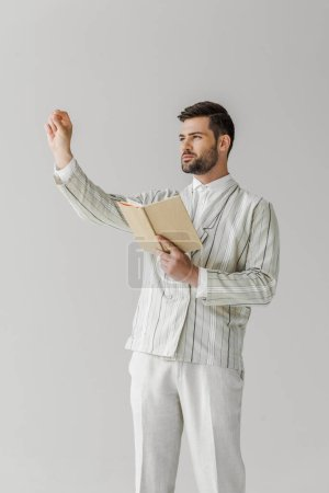 religious young man with bible making sign of cross isolated on white