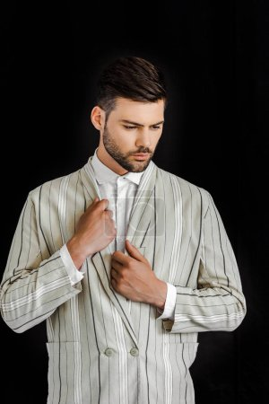 handsome young man in stylish striped jacket isolated on black