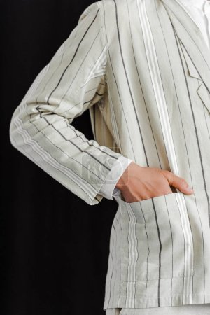 cropped shot of man with hand in pocket of stylish striped jacket isolated on black