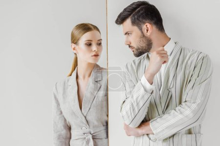 passionate young male and female models in vintage jackets looking at each other on white