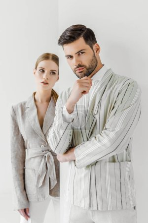 attractive young male and female models in vintage jackets on white